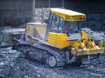 运转在工厂的黄色拖拉机 库存图片