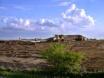 运转在废地面开垦的挖掘者和倾销者卡车 库存照片