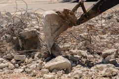 运转在废墟的挖掘机 免版税库存图片