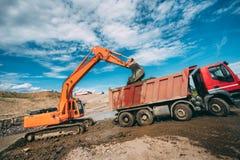 运转在建造场所-挖掘机装货在长跑训练期间的倾销者卡车的大量手段在高速公路 库存图片