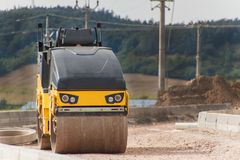 运转在新的修路站点的压路机 在一个空的建造场所的建筑机器 免版税库存图片