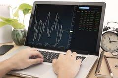 运转在有财务贸易的计算机笔记本的企业手 库存图片