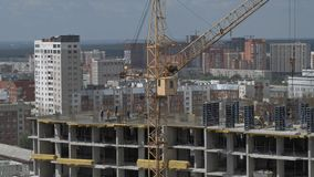 运转在未完成的居民住房工地工作的建造者和起重机 股票录像