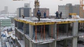 运转在未完成的居民住房工地工作的建造者和起重机 影视素材