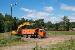 运转在清除的黄色挖掘机瓦砾 放地球入翻斗车在一个晴天 免版税库存图片