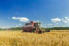 运转在燕麦农田的现代联合收割机在蓝天下在热的夏日 免版税库存照片