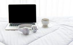 运转在白色床和咖啡上的膝上型计算机在晴天早晨假日 免版税库存照片