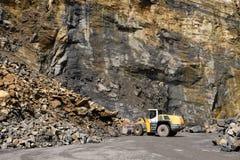 运转在石头大堆的轮子装载者机器在岩石面孔前面的在猎物 免版税库存照片