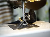 运转在缝纫机的手 图库摄影