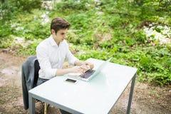 运转在膝上型计算机的白色衬衣的商人在办公桌在绿色公园 到达天空的企业概念金黄回归键所有权 免版税库存图片
