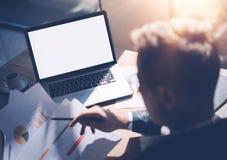 运转在膝上型计算机的晴朗的办公室的镜片的成人银行分析人员,当坐在木桌上时 商人分析 库存图片