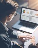 运转在膝上型计算机的晴朗的办公室的镜片的年轻金融市场分析家,当坐在木桌上时 商人 免版税图库摄影