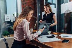 运转在膝上型计算机键入的电子邮件的年轻女性佩带的正装坐在她的工作场所 库存图片