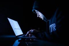 运转在膝上型计算机黑客裂化的节目前面的敞篷的人夜 库存照片