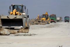 运转在跑道建造场所的重型建筑设备 免版税图库摄影