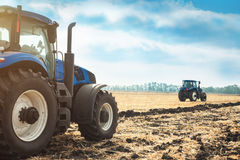 运转在领域的两台拖拉机 免版税库存图片