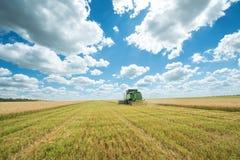 运转在麦子庄稼的联合收割机 图库摄影
