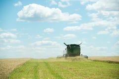 运转在麦子庄稼的联合收割机 免版税库存照片