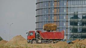 运转在建造场所的建筑机械:平地机装载沙子入翻斗车 股票录像