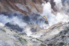 运转在Jigokudani, Noboribetsu,北海道的挖掘机 围拢由从valcano区域的硫磺气体 库存图片
