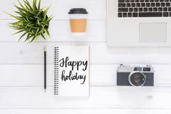 运转的书桌平的位置视图照片有愉快的假日愿望笔记本、咖啡杯、照相机和膝上型计算机的在白色木背景 免版税图库摄影