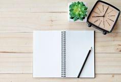 运转的书桌顶视图有空白的笔记本的有铅笔、减速火箭的闹钟和植物的木背景的 免版税库存照片