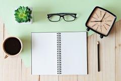 运转的书桌顶视图有空白的笔记本的有铅笔、咖啡杯、镜片、减速火箭的闹钟和植物的木背景的 图库摄影