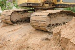 运转的挖掘机肮脏的履带牵引装置在沙子的 库存照片