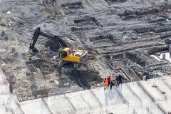 运转的挖掘机鸟瞰图有建造者的站立近 免版税库存照片