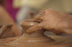 运转黏土的陶瓷工手 库存照片