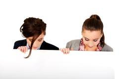 运载一个大白板的两名女实业家 库存图片