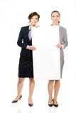 运载一个大白板的两名女实业家 免版税库存图片