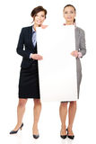 运载一个大白板的两名女实业家 免版税库存照片