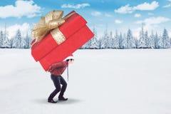 运载一个大礼物盒的年轻商人 图库摄影