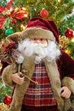 运载一个大袋袋子有圣诞树背景的圣诞老人 库存照片