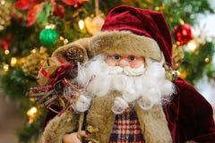 运载一个大袋袋子有圣诞树背景的圣诞老人 免版税图库摄影
