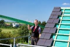 运载一个木粱的盖屋顶的人 免版税库存照片