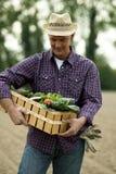 运载一个条板箱蔬菜的农夫 免版税库存照片