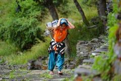 运载一个篮子的一名年轻Gurung夏尔巴妇女在喜马拉雅山 库存照片