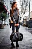 运载一个重的黑提包的深色的妇女 库存照片