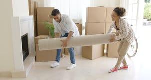 运载一个滚动的地毯的年轻夫妇入房子 图库摄影