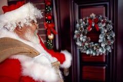 运载与礼物的圣诞老人大袋子在夜 免版税库存照片