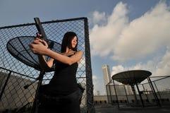 运载中国女孩手枪的亚洲人 免版税库存图片