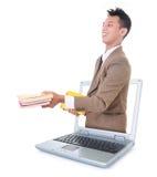 运载书的商人和在膝上型计算机外面 免版税库存图片
