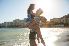 运载他的女朋友的愉快的人站立在水中 库存图片