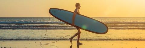 运载他的水橇板家的冲浪者的假期剪影在与拷贝空间横幅的日落,长的格式 免版税库存图片