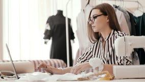 运载卷尺和工作在纺织品工厂的一位美丽的裁缝的画象 影视素材