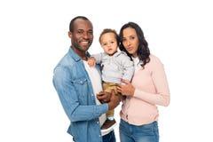 运载可爱的矮小的儿子和微笑对照相机的愉快的非裔美国人的父母 免版税库存照片