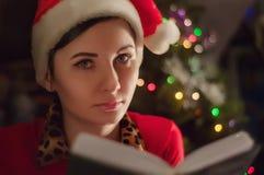 运载圣诞节克劳斯礼品例证晚上圣诞老人向量 在读圣诞节故事的树女孩附近 库存照片