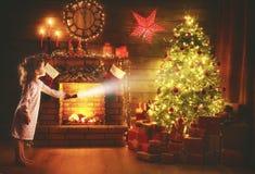 运载圣诞节克劳斯礼品例证晚上圣诞老人向量 有一个手电的女婴在看fo的晚上 免版税库存照片
